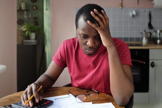 medical debt collections; stressed man looking over his medical bills