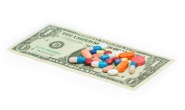 préstamos y financiación médica; billete de un dólar con pastillas en la parte superior