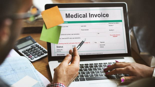 medical debt; people looking at a medical invoice on a laptop screen