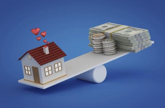 línea de crédito con garantía hipotecaria; casa equilibrando con dinero en una tabla