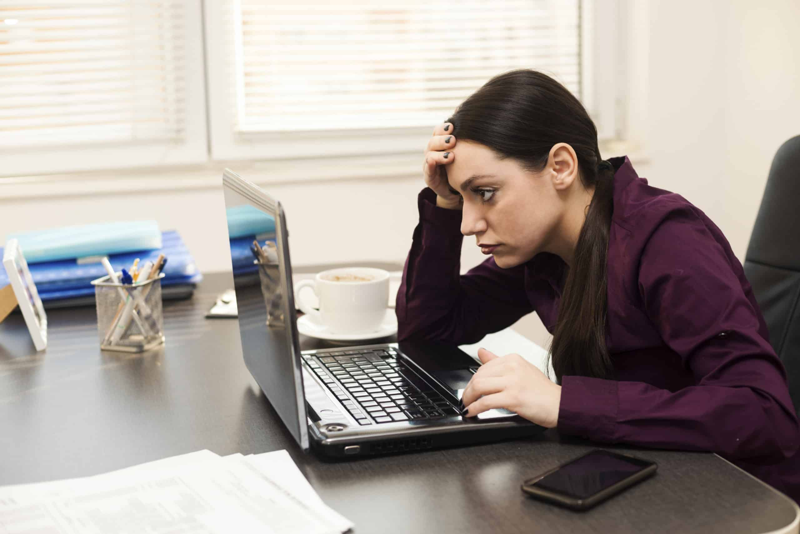 surviving a layoff; woman looking stressed in front of her laptop