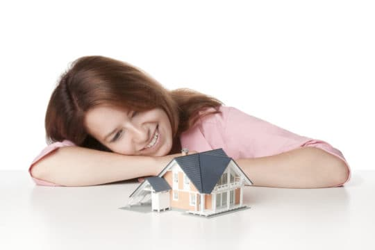 home equity loans; woman looking at small model home