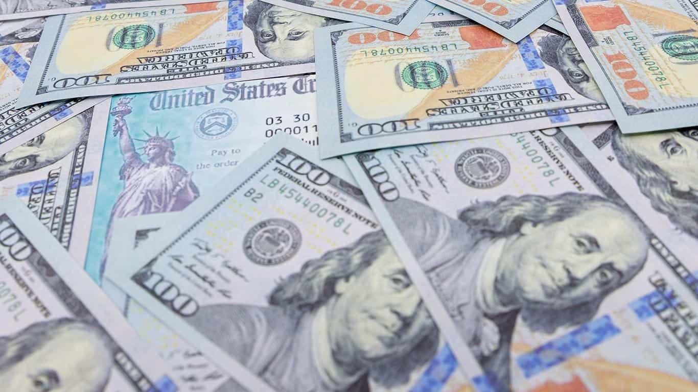 Stack of 100 dollar bills with coronavirus.