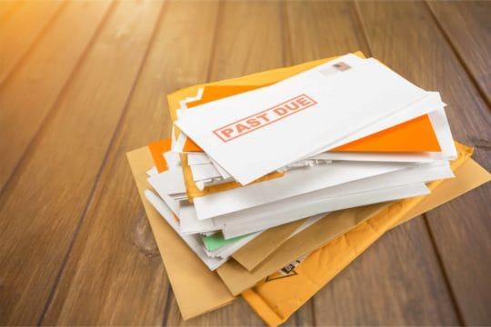 A pile of mail with past due notifications
