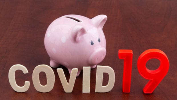 Save money in coronavirus covid-19 time concept. Piggy bank and word covid19 close up.