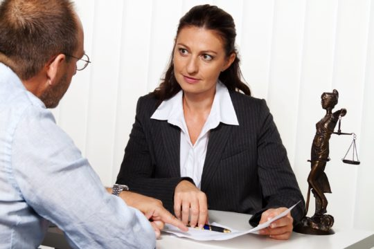 debt collection attorney; woman attorney sitting down with her client in debt
