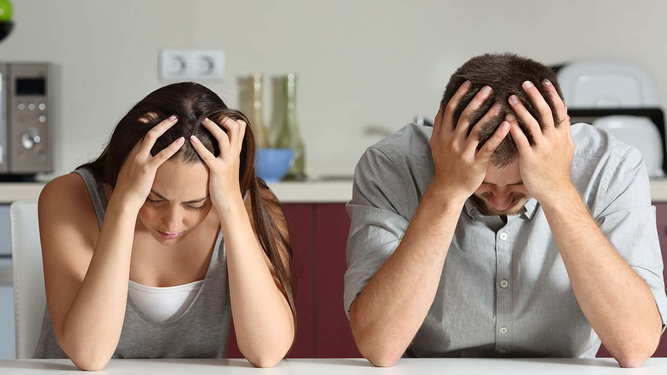 Front view of a sad couple with hands on head sitting in the kitchen of a house