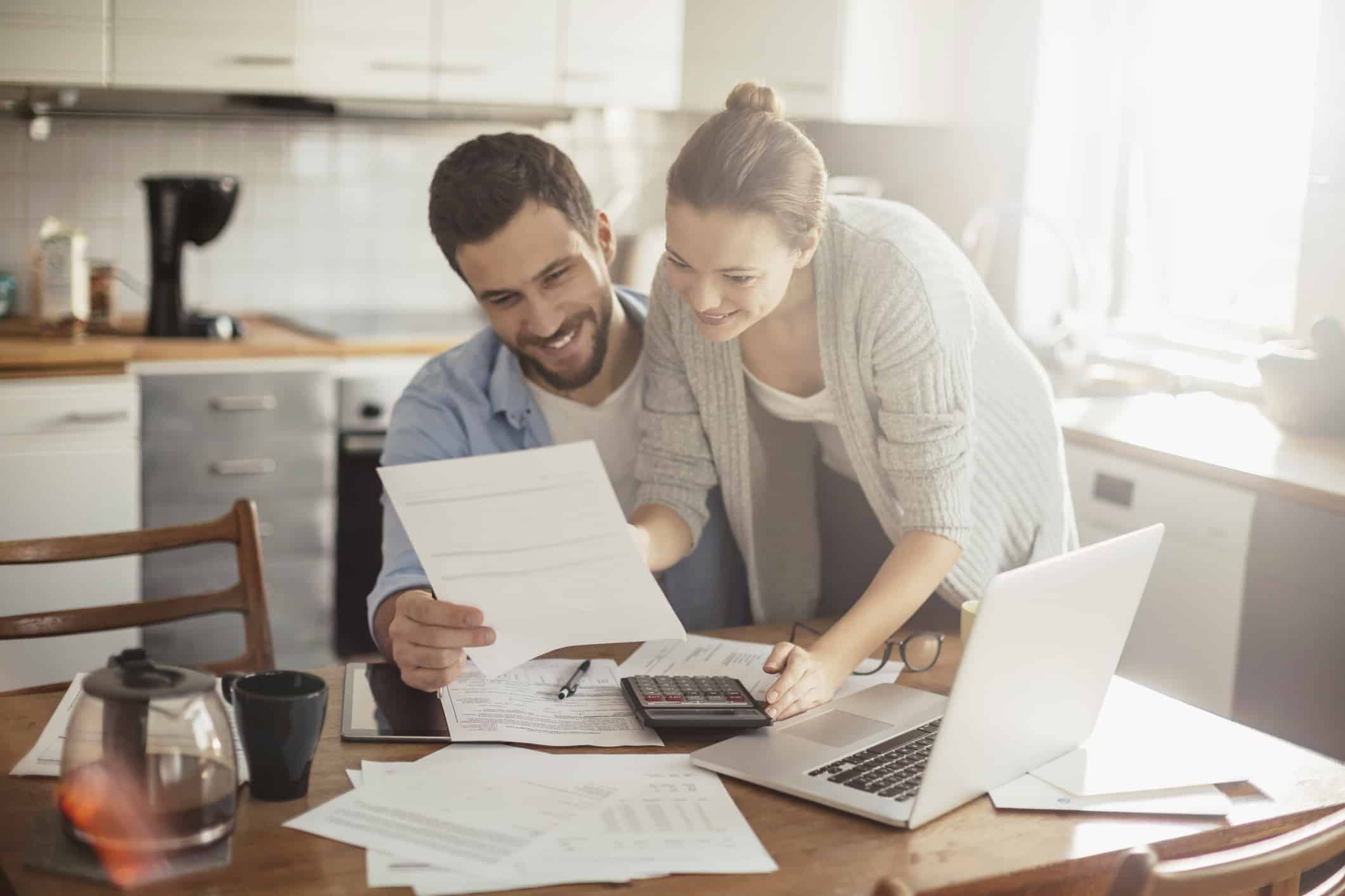 debt consolidation program; couple looking at debt management documents at laptop