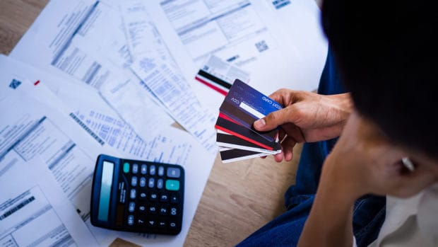 Business people are stressed about credit card debt and many bills on the floor.