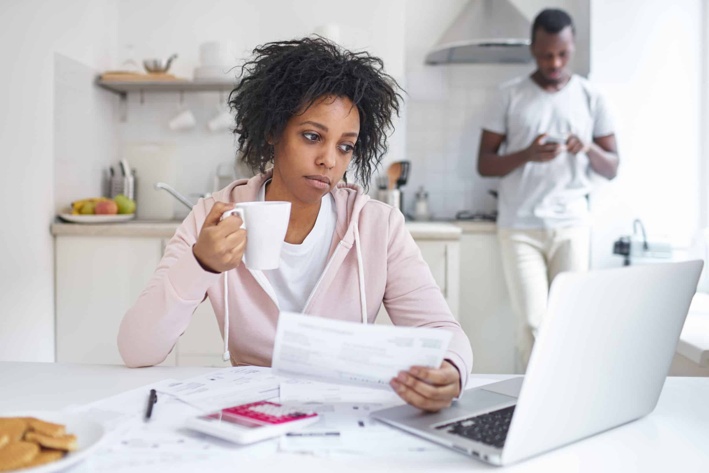 dating with debt; tired woman at her laptop looking at bills while her husband stands in the kitchen