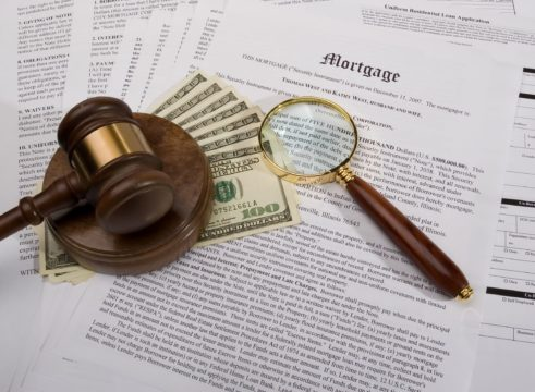 fixed rate mortgage guide; money, gavel, and magnifying glass on top of mortgage papers