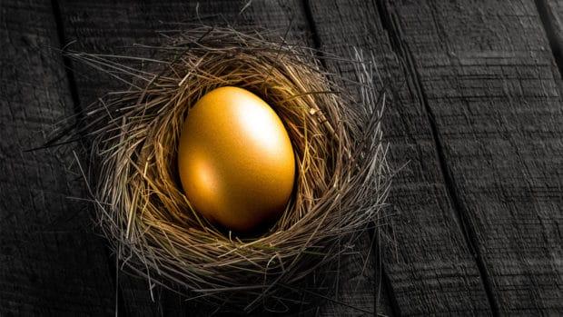 Golden Nest Egg On Wooden Table
