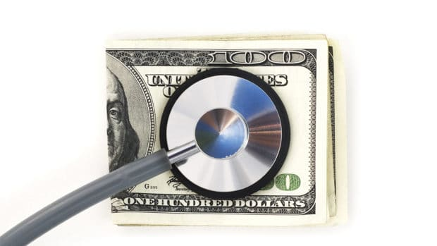 Stethoscope with hundred dollar bills on a white background. Financial check up.