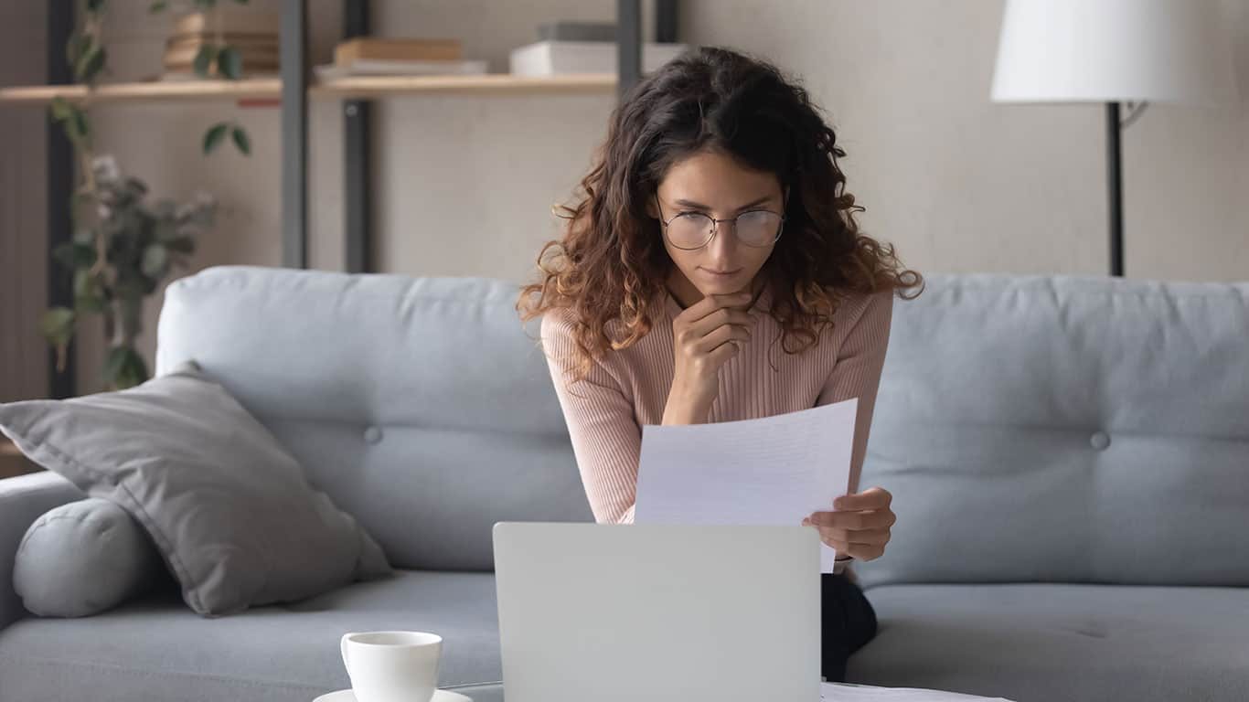 Thoughtful woman wearing glasses reading document, using laptop