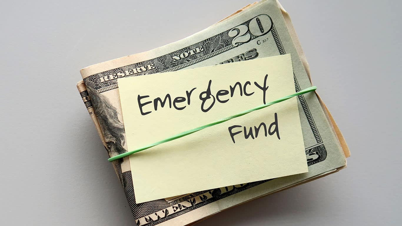 Dollars Money and paper note with text written on EMERGENCY FUND on background with copy space - concept of financial planning saving money