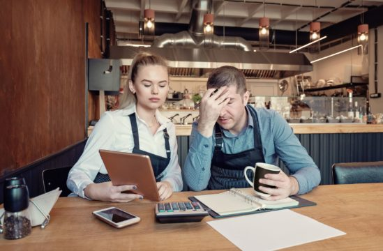 small business bankruptcy; white man and woman discussing business finances with aprons on in a cafe