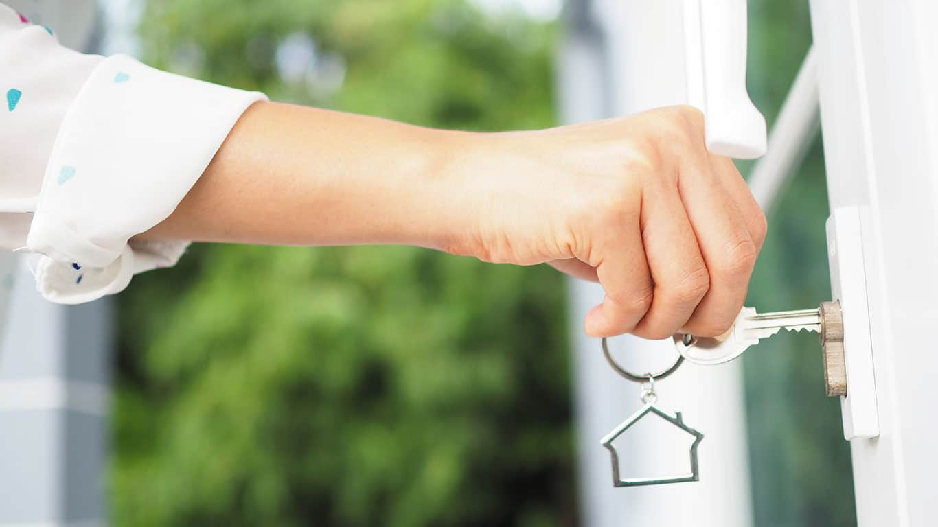 The female hand is using the key to open his own house