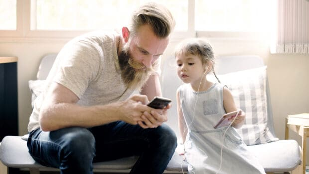 Single father looking at his phone while his daughter looks on