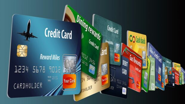 Credit cards and debit cards stacked together to represent having too many credit cards recompensas de tarjetas de crédito