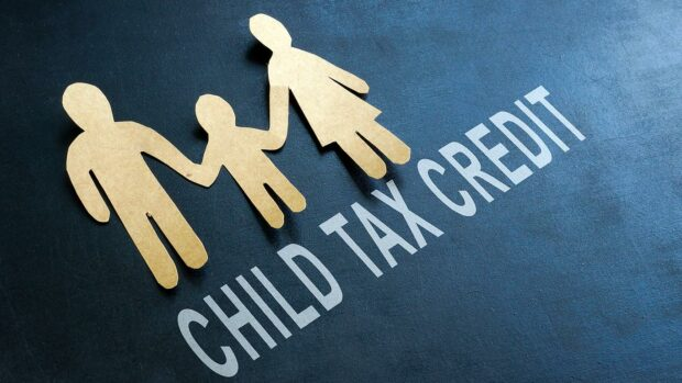 Paper family and words child tax credit on the blackboard