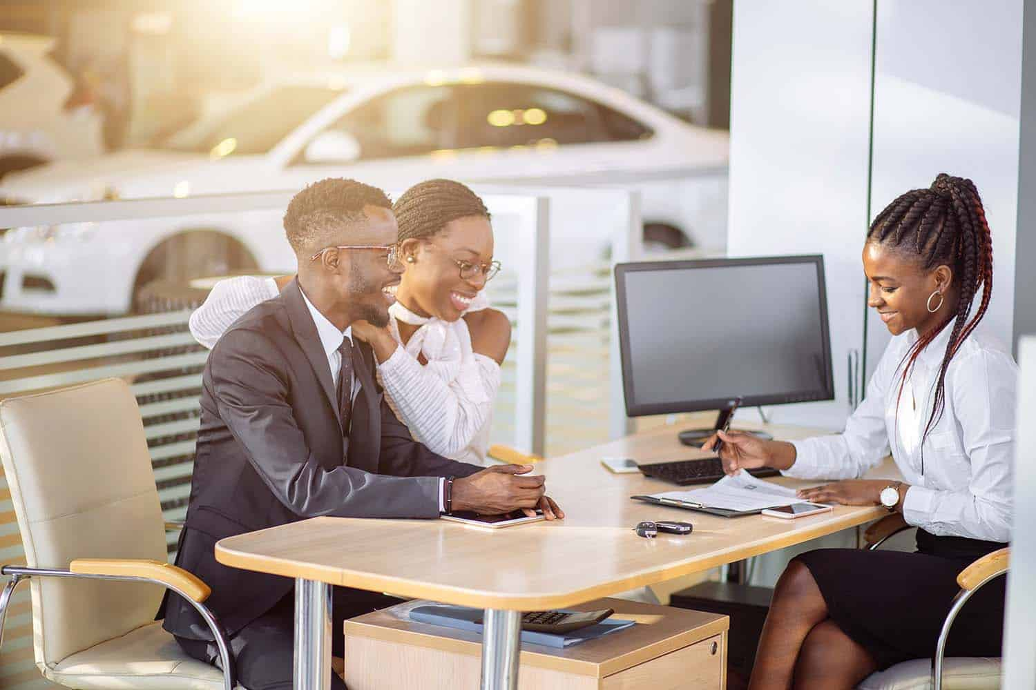 African American couple sitting down and signing an auto loan with their dealer at the dealership