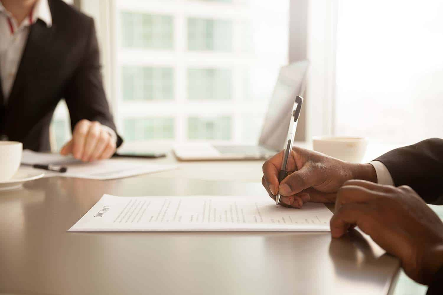 African American man signing car lease buyout contract