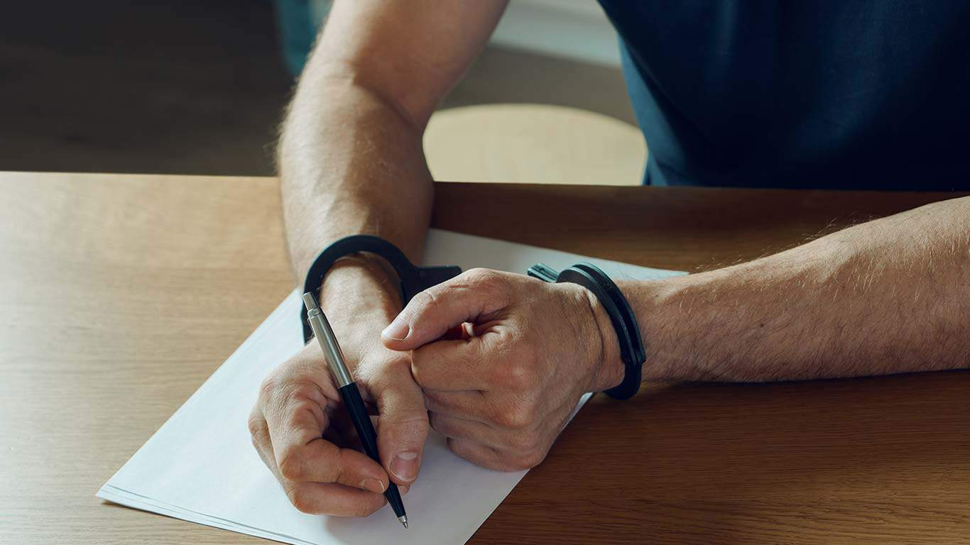 Men hands with handcuffs fill the police record, confession.